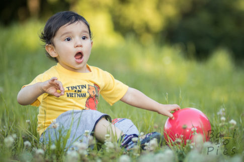 Kid with red ball in forest