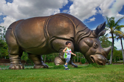 Kid with rhinoceros in GWK Cultural Park - Bali